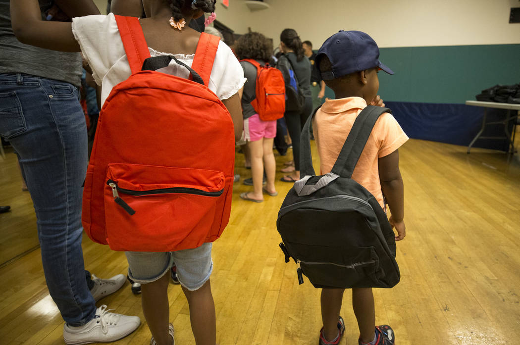 Children try on their new book bags during a back-to-school fair hosted by the Metropolitan Police Department held at the Dula Gymnasium in downtown Las Vegas on Saturday, Aug. 12, 2017. Richard B ...