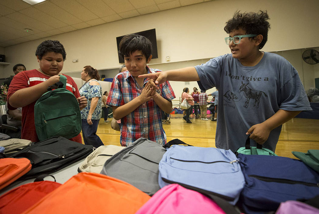 Las Vegas residents Javier Munguia, from left, Roberto Munguia and Brallan Munguia pick out their favorite backpacks during a back-to-school fair hosted by the Metropolitan Police Department held  ...