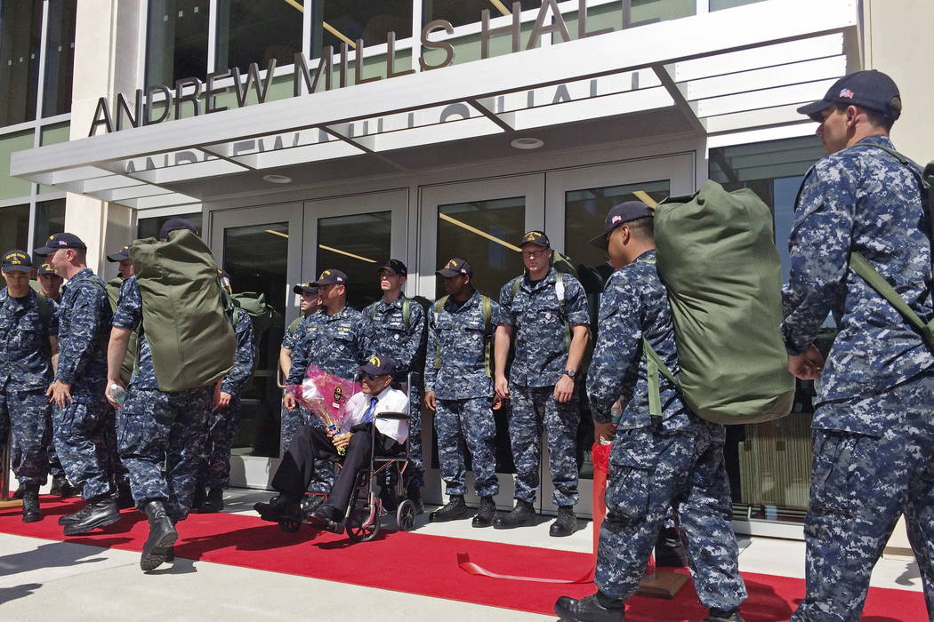 Former Navy Chief Steward Andy Mills, 102, seated in wheelchair, watches as sailors carrying their seabags check into their new barracks, named in honor of Mills, at Naval Base Coronado, Calif., T ...