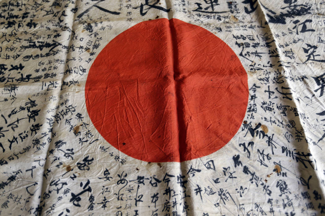 In this Monday, Aug. 7, 2017 photo, names are visible on a Japanese flag owned by WWII veteran Marvin Strombo in Portland, Ore. Strombo recovered the flag from a dead Japanese soldier in the Pacif ...