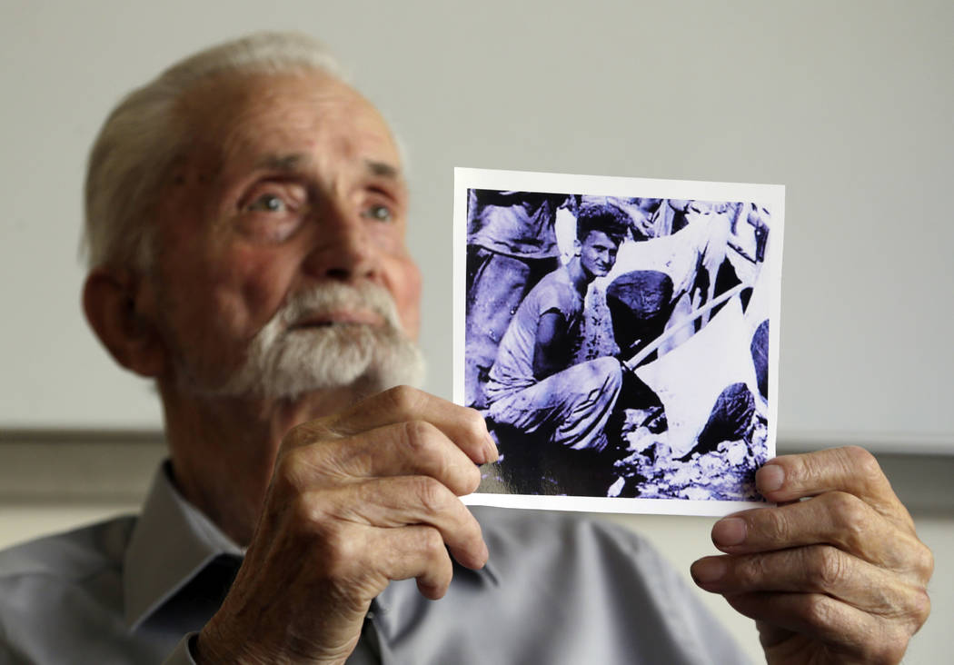 In this Monday, Aug. 7, 2017 photo, WWII veteran Marvin Strombo holds up a photo of himself taken during the battle on Saipan with him holding a captured sword and flag in Portland, Ore. Strombo r ...