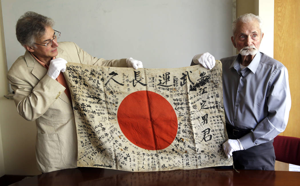In this Monday, Aug. 7, 2017 photo, WWII veteran Marvin Strombo, right, and Obon Society executives director Rex Zika hold up a Japanese flag with names written on it in Portland, Ore. Strombo rec ...