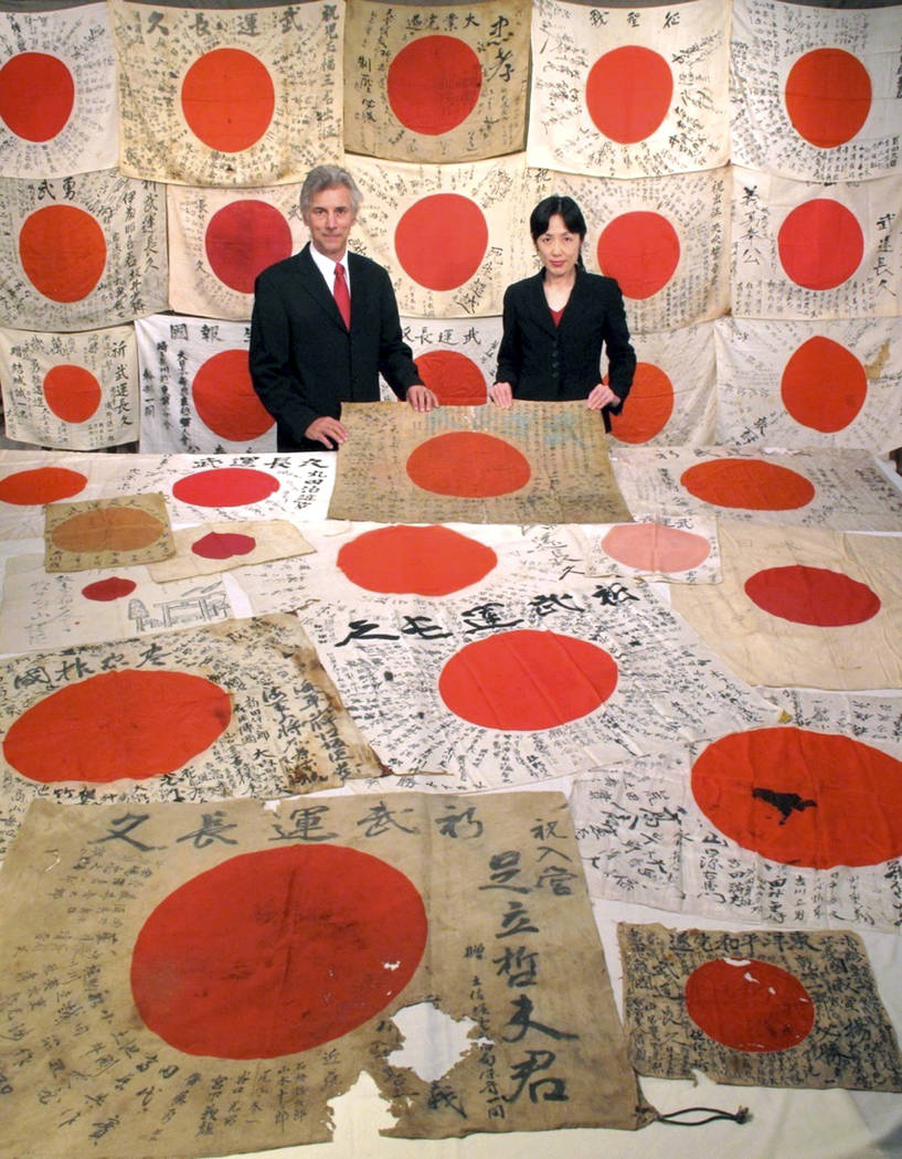 In this Monday, Aug. 7, 2017 photo, Obon Society founders Rex and Keiko Ziak pose with a collection of WWII-era Japanese flags, gathered from dead Japanese soldiers by American soldiers, in Portla ...