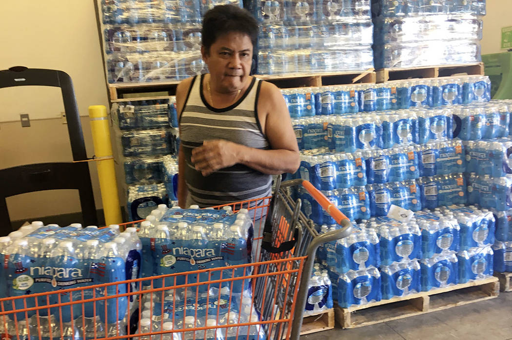 A resident buys bottles of water at Home Depot in Guam Saturday, Aug. 12, 2017.  (AP Photo/Tassanee Vejpongsa)