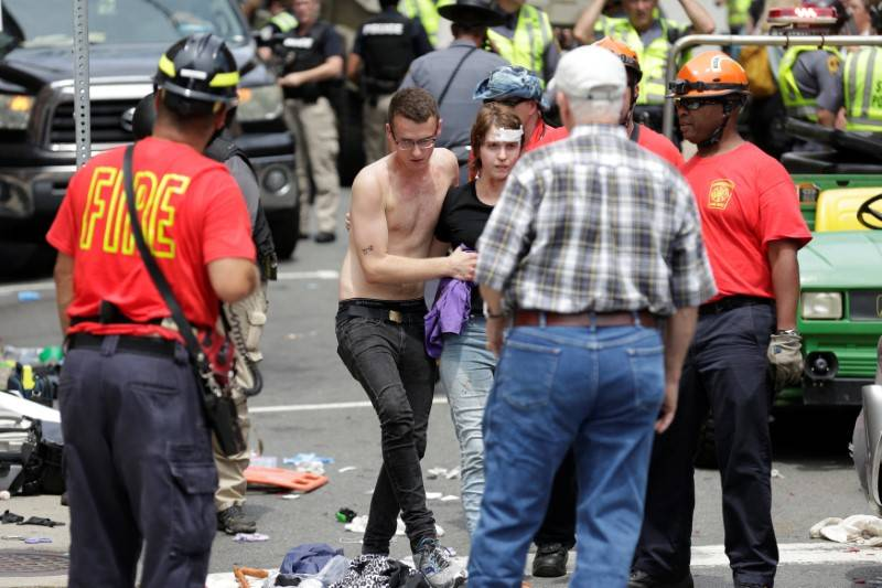"""A woman who was injured when a car drove through a group of counter protestors at the """"Unite the Right"""" rally is helped in Charlottesville, Virginia, U.S., August 12, 2017.   REU ..."""
