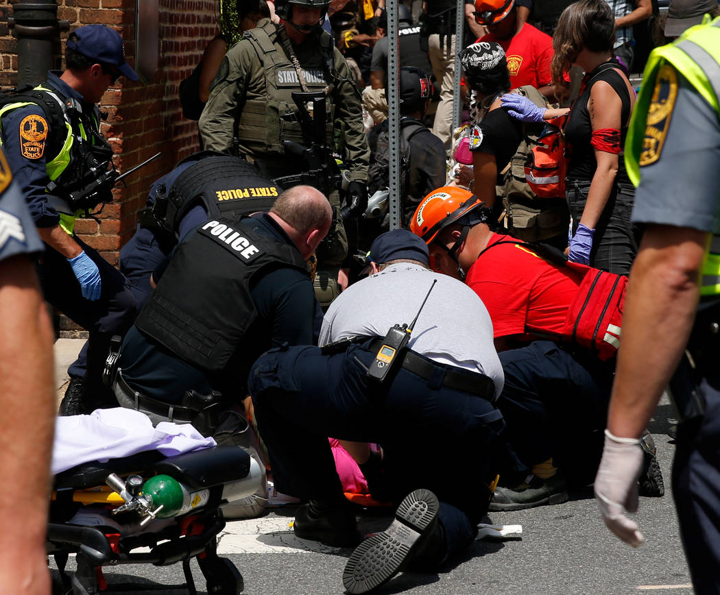 """Rescue workers assist people who were injured when a car drove through a group of counter protestors at the """"Unite the Right"""" rally Charlottesville, Virginia, U.S., August 12, 20 ..."""