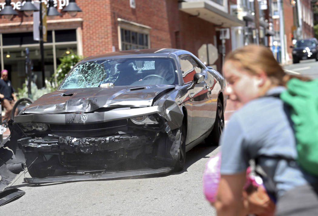 A vehicle reverses after driving into a group of protesters demonstrating against a white nationalist rally in Charlottesville, Va., Saturday, Aug. 12, 2017. The nationalists were holding the rall ...
