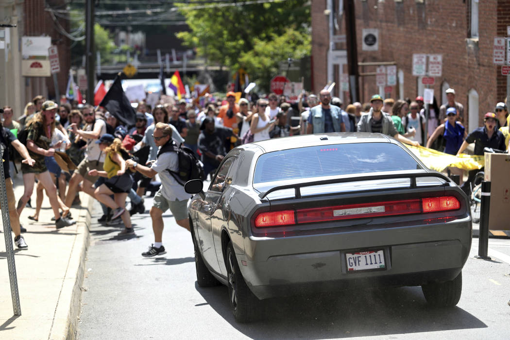 A vehicle drives into a group of protesters demonstrating against a white nationalist rally in Charlottesville, Va., Saturday, Aug. 12, 2017. The nationalists were holding the rally to protest pla ...