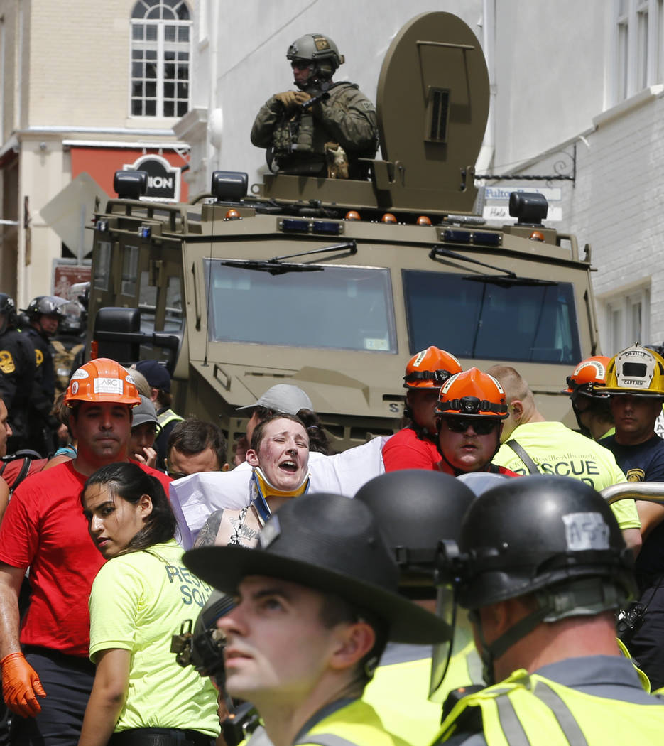 Rescue personnel help injured people after a car ran into a large group of protesters after an white nationalist rally in Charlottesville, Va., Saturday, Aug. 12, 2017. The nationalists were holdi ...