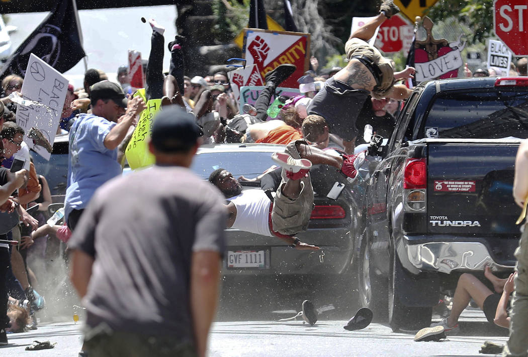 People fly into the air as a vehicle drives into a group of protesters demonstrating against a white nationalist rally in Charlottesville, Va., Saturday, Aug. 12, 2017. The nationalists were holdi ...