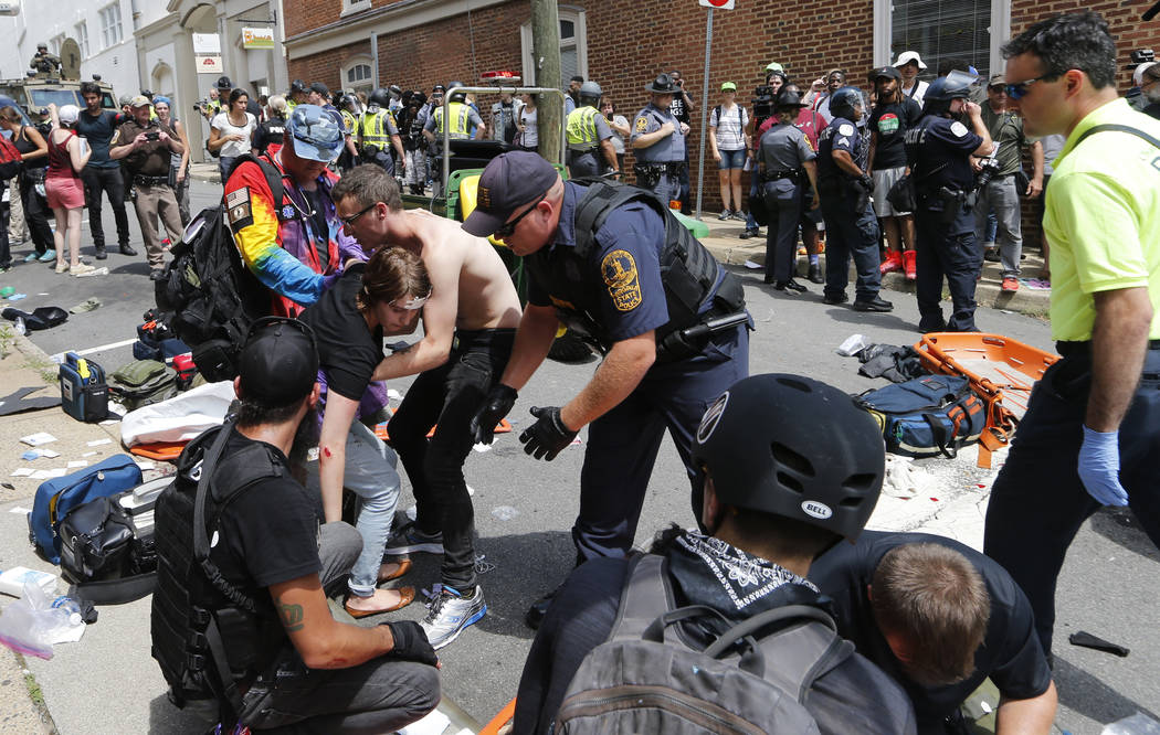 Rescue personnel help injured people after a car ran into a large group of protesters after a white nationalist rally in Charlottesville, Va., Saturday, Aug. 12, 2017. The nationalists were holdin ...