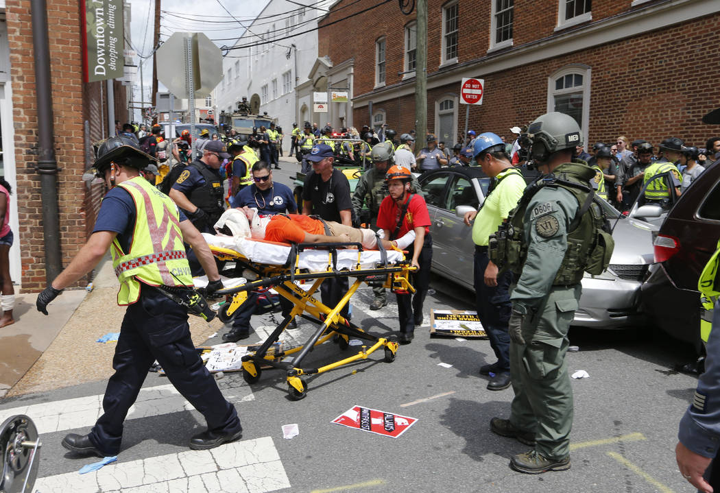 Rescue personnel help injured people after a car ran into a large group of protesters after an white nationalist rally in Charlottesville, Va., Saturday, Aug. 12, 2017.  The nationalists were hold ...