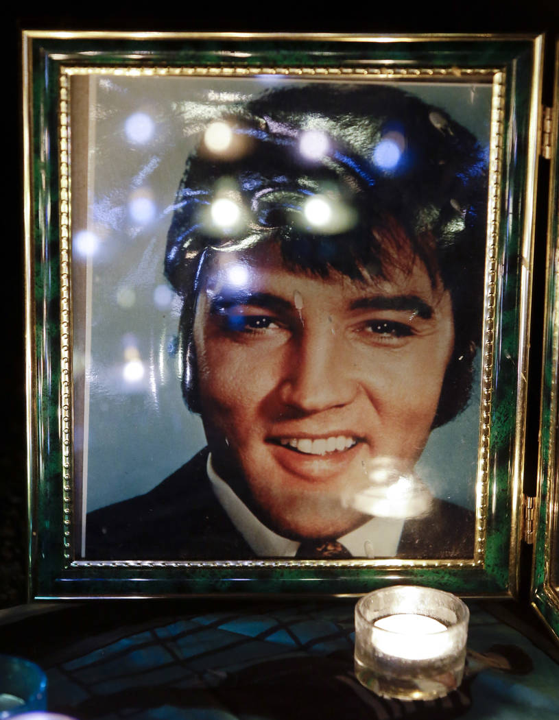 Candles reflected in a photo of Elvis Presley at a memorial set up by a fan at a candlelight vigil at Graceland, Presley's Memphis, Tenn. home on Aug. 15, 2012. (AP Photo/Mark Humphrey, File)