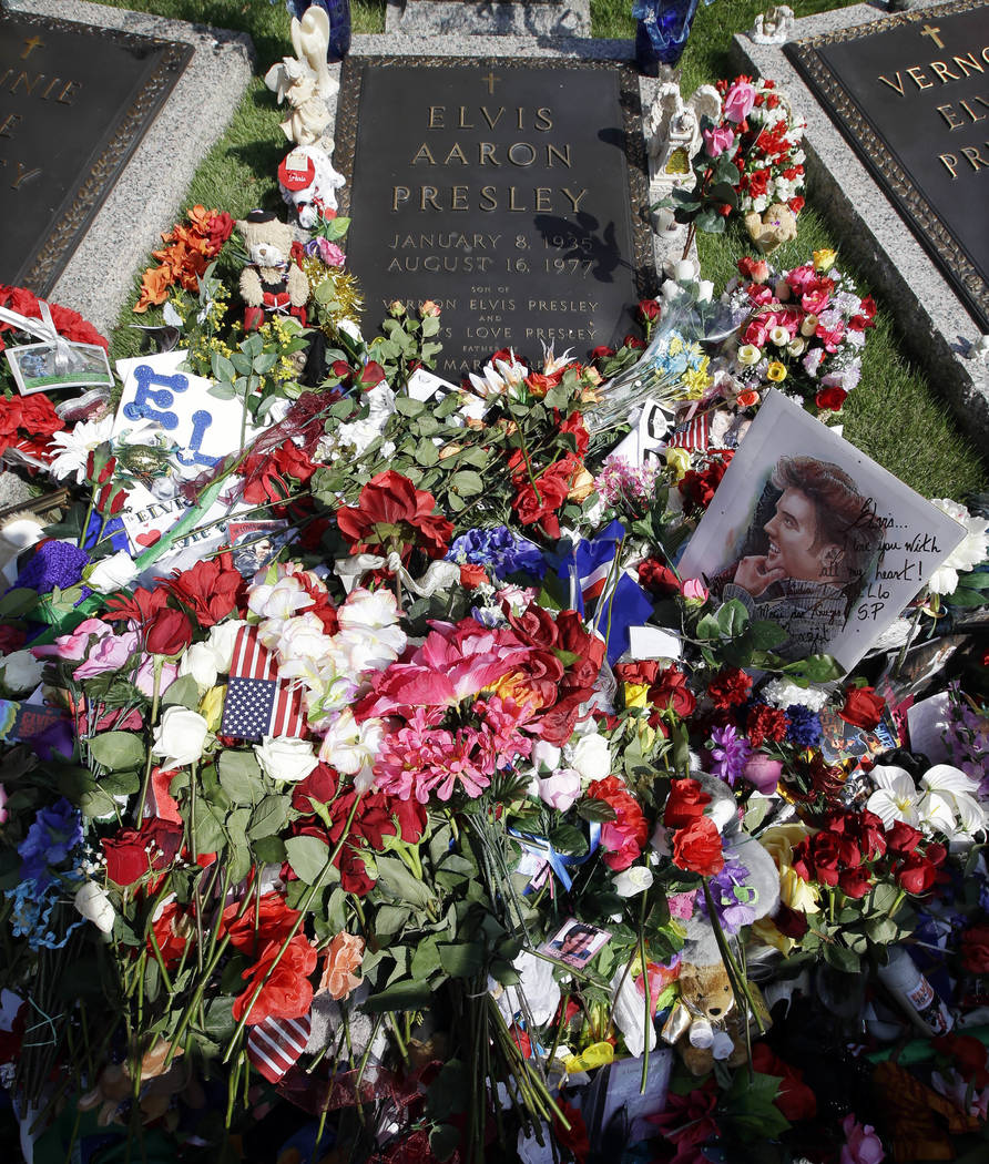 Flowers left by fans on the grave of Elvis Presley at Graceland, Presley's Memphis, Tenn. home on Aug. 16, 2012. (AP Photo/Mark Humphrey, File)