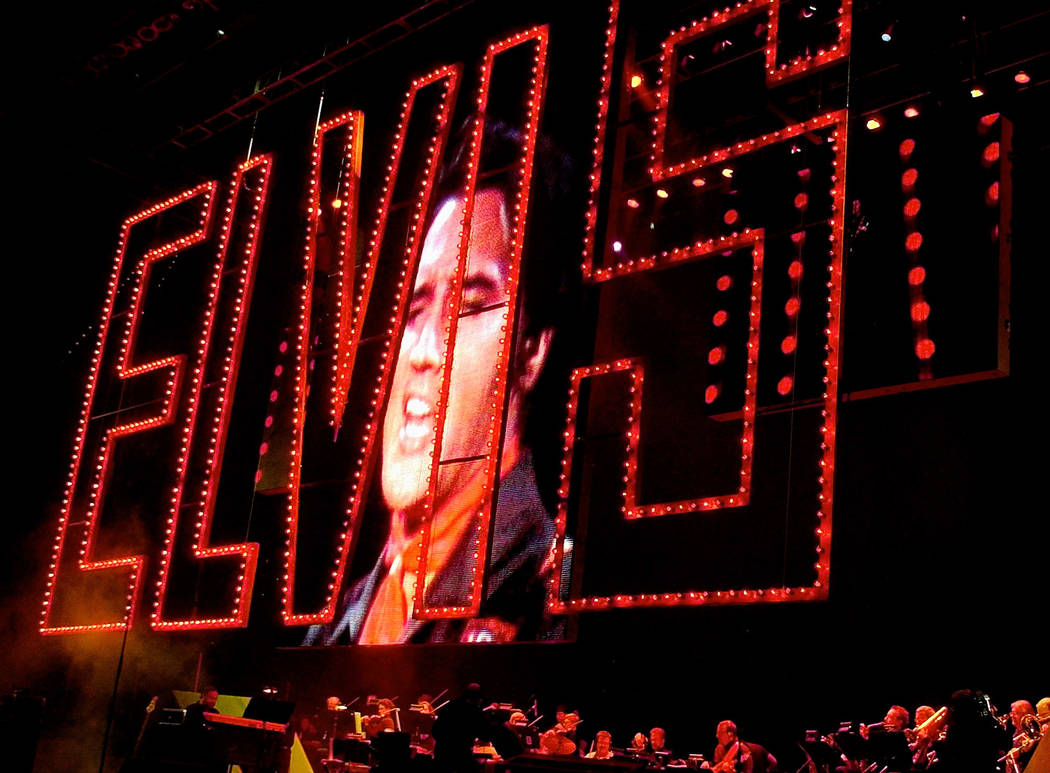 An image of Elvis Presley singing as his band plays below at the start of the Elvis Presley 25th Anniversary Concert in Memphis, Tenn. on Aug. 16, 2002. The red Elvis sign is from the 1968 Elvis ' ...