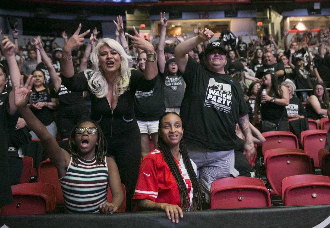 Fans cheer and pose for the camera while trying to snag apparel thrown into the stands during the Raiders Watch Party at the Thomas and Mack Center in Las Vegas, Saturday, Aug. 12, 2017. Gabriella ...
