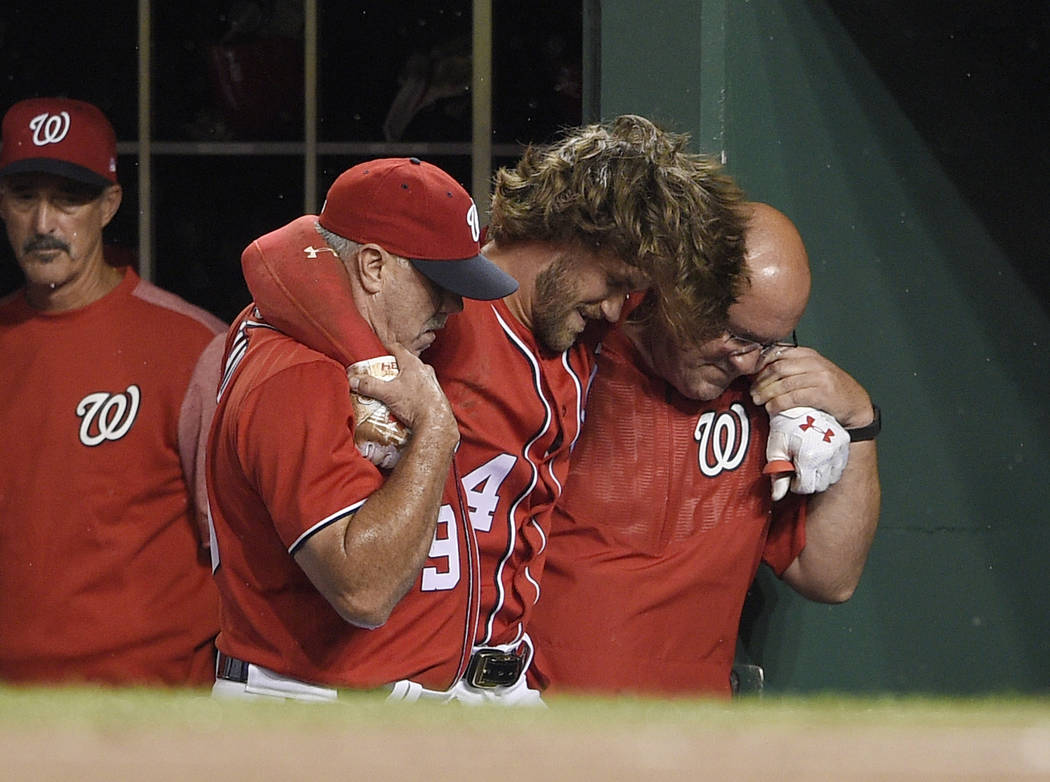 Washington Nationals' Bryce Harper, center, is helped in the dugout after he was injured during the first inning of the team's baseball game against the San Francisco Giants, Saturday, Aug. 12, 20 ...