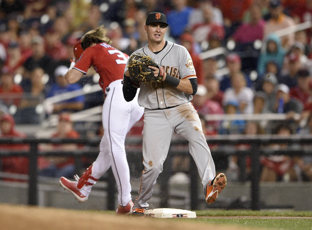 Washington Nationals' Bryce Harper, back, is put out at first by San Francisco Giants third baseman Ryder Jones during the first inning of a baseball game, Saturday, Aug. 12, 2017, in Washington.  ...
