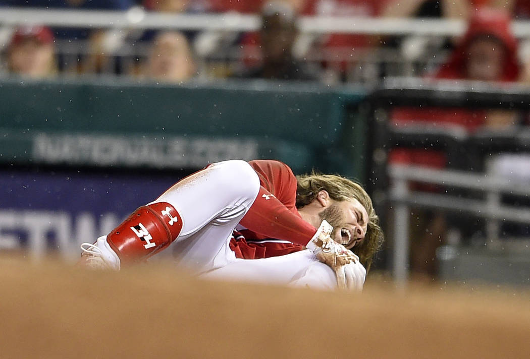 Washington Nationals' Bryce Harper grabs his knee after he was injured running to first during the first inning of the team's baseball game against the San Francisco Giants, Saturday, Aug. 12, 201 ...
