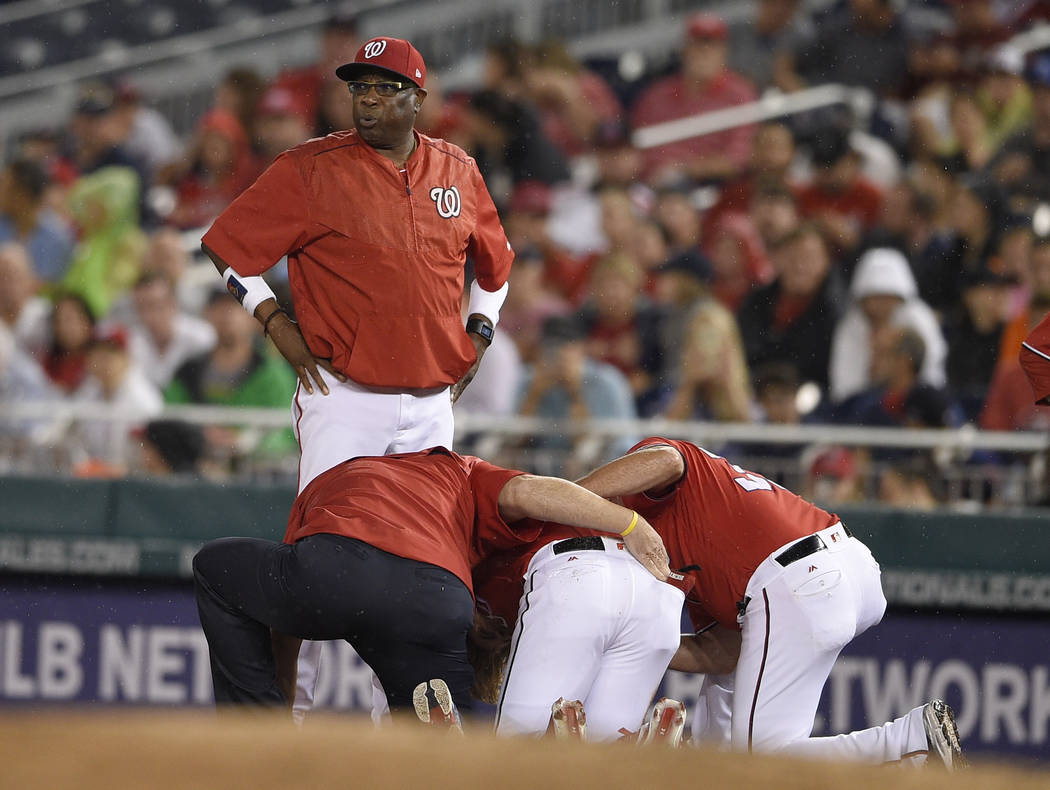 Washington Nationals manager Dusty Baker, top, stands on the field as Bryce Harper, bottom center, receives attention after he was injured during the first inning of a baseball game against the Sa ...