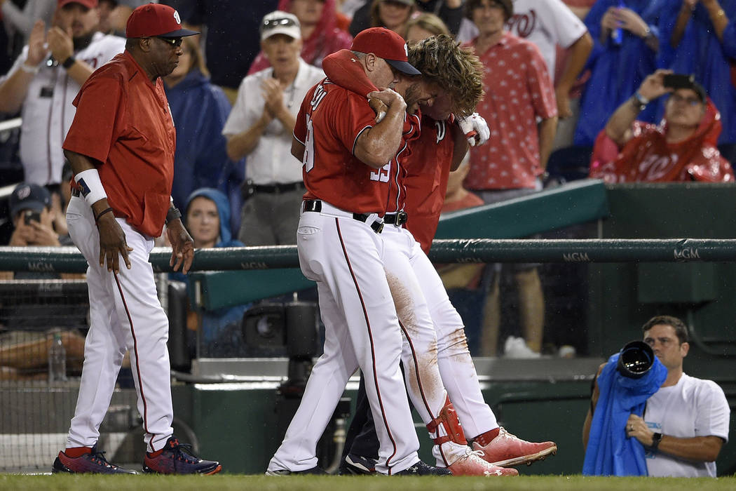 Washington Nationals' Bryce Harper, second from right, is helped off the field after he was injured during the first inning of a baseball game against the San Francisco Giants, Saturday, Aug. 12,  ...