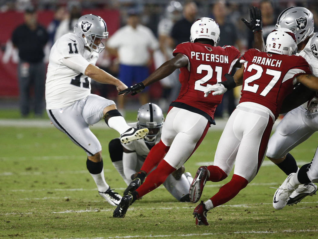 Oakland Raiders kicker Sebastian Janikowski (11) misses a field goal attempt as Arizona Cardinals cornerback Patrick Peterson (21) defends during the first half of an NFL preseason football game,  ...