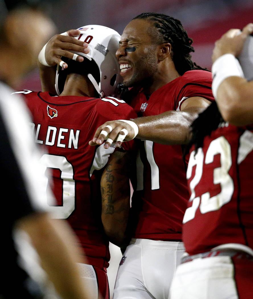 Arizona Cardinals wide receiver Larry Fitzgerald hugs teammate Brittan Golden (10) after Golden scored a touchdown against the Oakland Raiders during the first half of an NFL preseason football ga ...