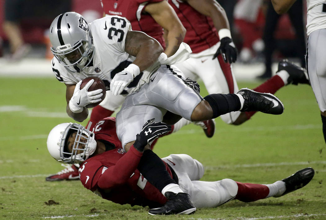 Oakland Raiders running back DeAndre Washington (33) is tackled by Arizona Cardinals cornerback Justin Bethel during the first half of an NFL preseason football game, Saturday, Aug. 12, 2017, in G ...