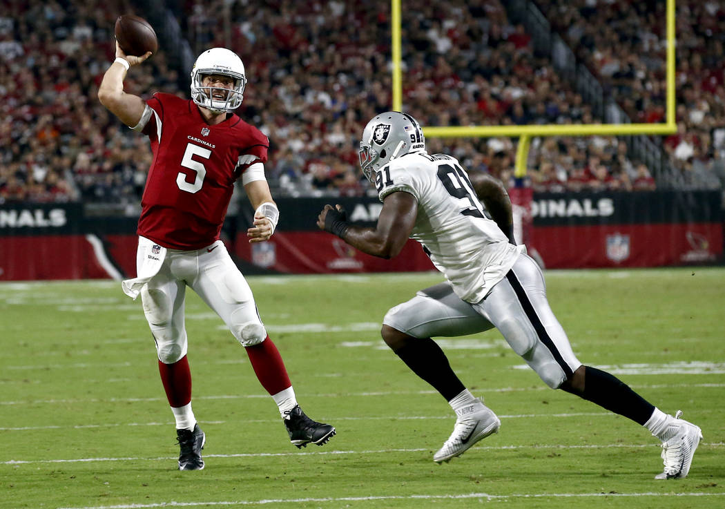 Arizona Cardinals quarterback Drew Stanton (5) throws for a touchdown as Oakland Raiders linebacker Shilique Calhoun (91) closes in during the first half of an NFL preseason football game, Saturda ...