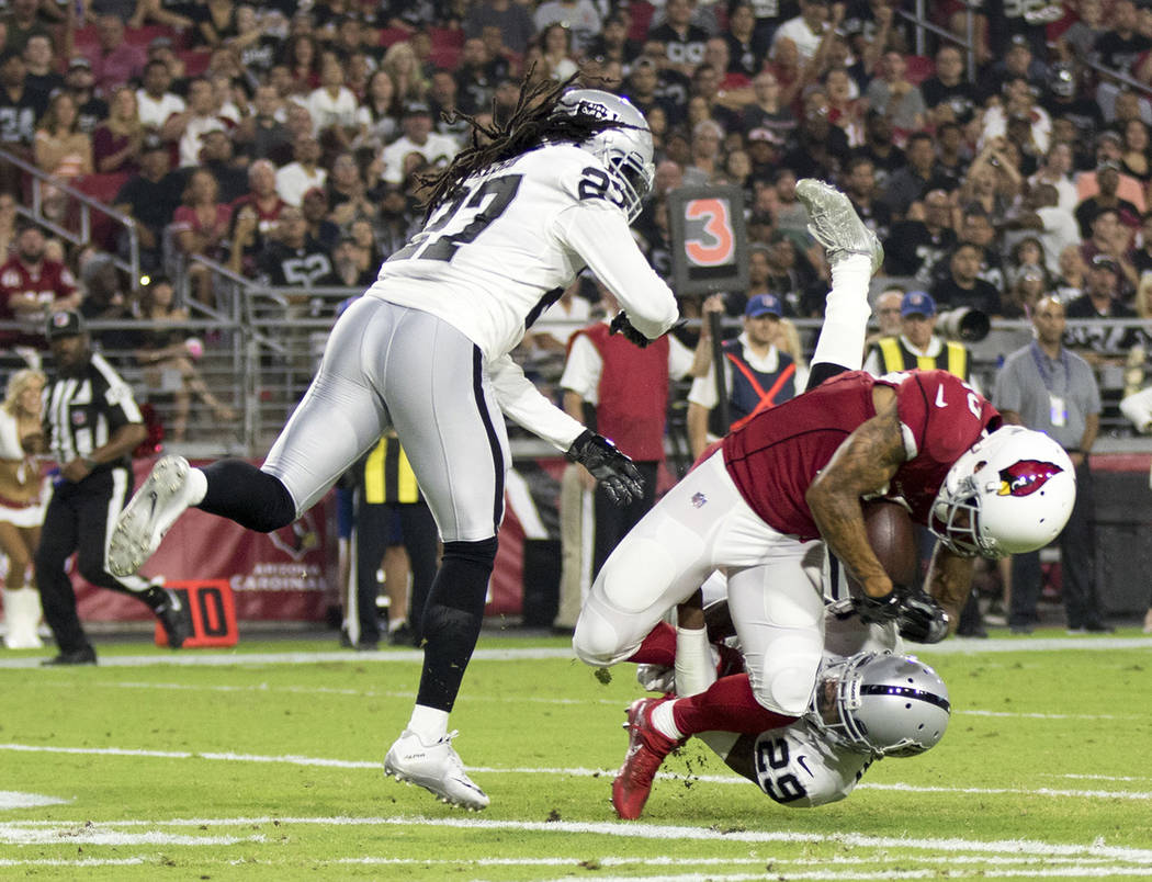 Arizona Cardinals wide receiver Brittan Golden (10) scores a touchdown over Oakland Raiders defenders Reggie Nelson (27) and David Amerson (29) during the first quarter of an NFL preseason game in ...