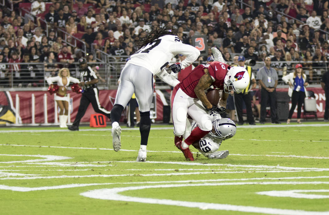 Arizona Cardinals wide receiver Brittan Golden (10) scores a touchdown over Raiders defenders Reggie Nelson (27) and David Amerson (29) during the first quarter of an NFL preseason game in Glendal ...