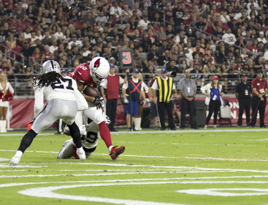 Arizona Cardinals wide receiver Brittan Golden (10) catches a touchdown over Raiders defenders Reggie Nelson (27) and David Amerson (29) during the first quarter of an NFL preseason game in Glenda ...