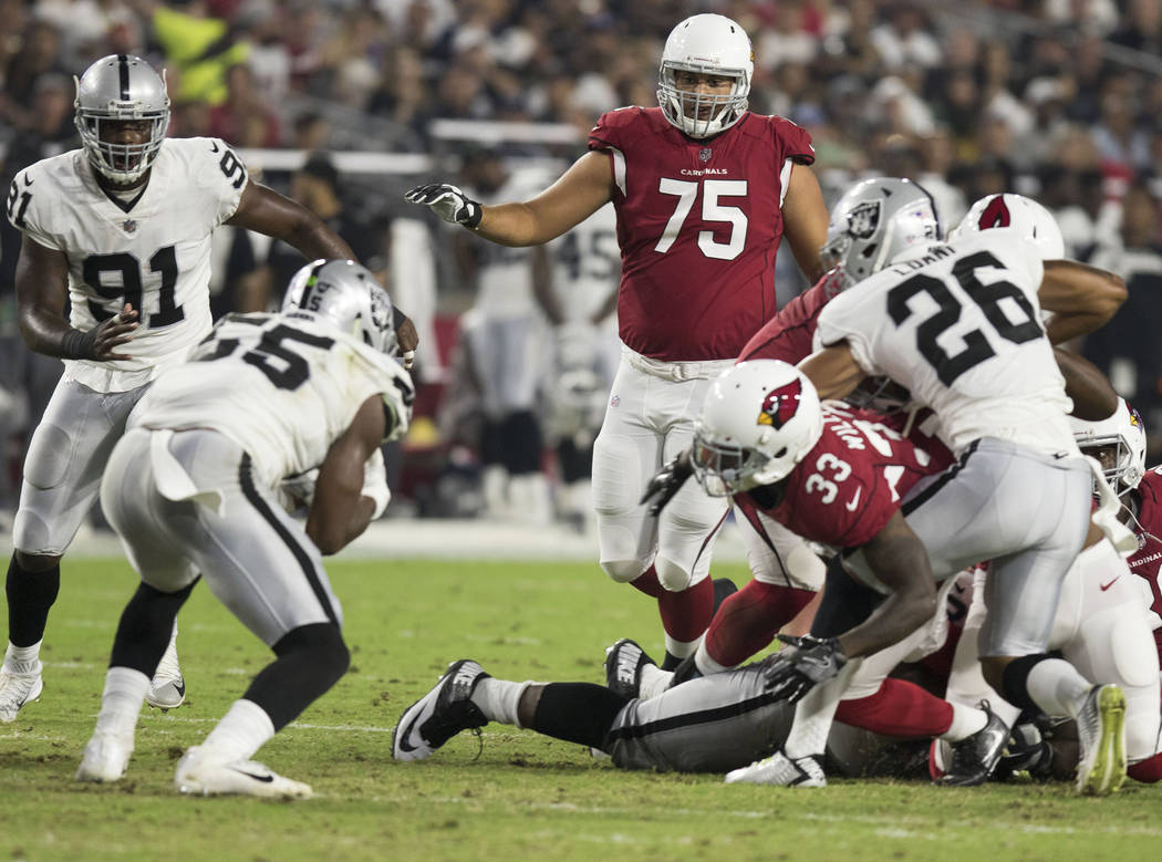 Oakland Raiders linebacker Marquel Lee (55) recovers a fumble made by Arizona Cardinals running back Kerwynn Williams (33) during the first quarter of an NFL preseason game in Glendale, Ariz., Sat ...
