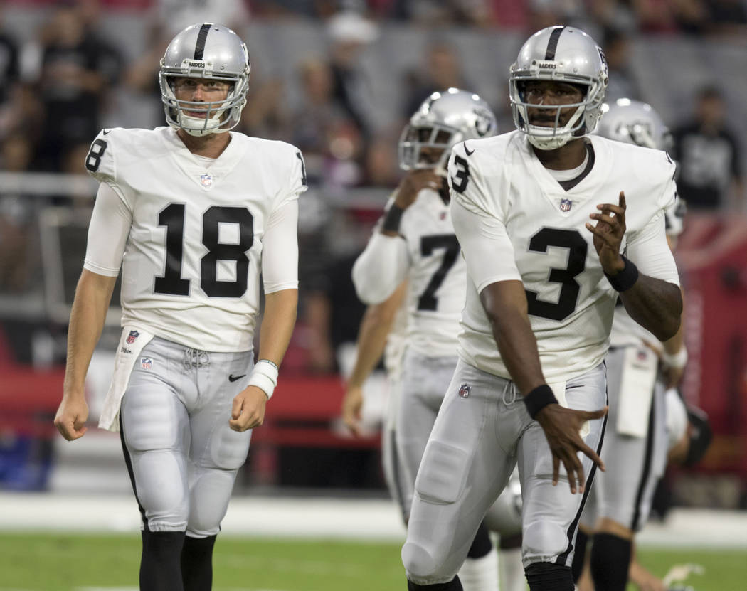 Oakland Raiders quarterbacks EJ Manuel (3) and Connor Cook (18) warm up ahead of the NFL preseason game against the Arizona Cardinals in Glendale, Ariz., on Saturday, August 12, 2017. Heidi Fang/L ...