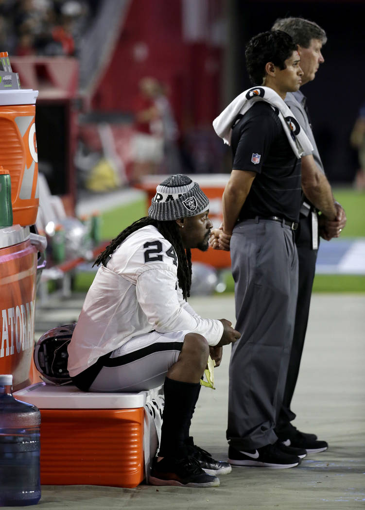 Oakland Raiders running back Marshawn Lynch (24) sits during the national anthem prior to an NFL preseason football game against the Arizona Cardinals, Saturday, Aug. 12, 2017, in Glendale, Ariz.  ...