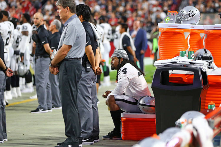 Aug 12, 2017; Glendale, AZ, USA;  Oakland Raiders running back Marshawn Lynch sits on a cooler on the bench during the national anthem prior to the game against the Arizona Cardinals at University ...