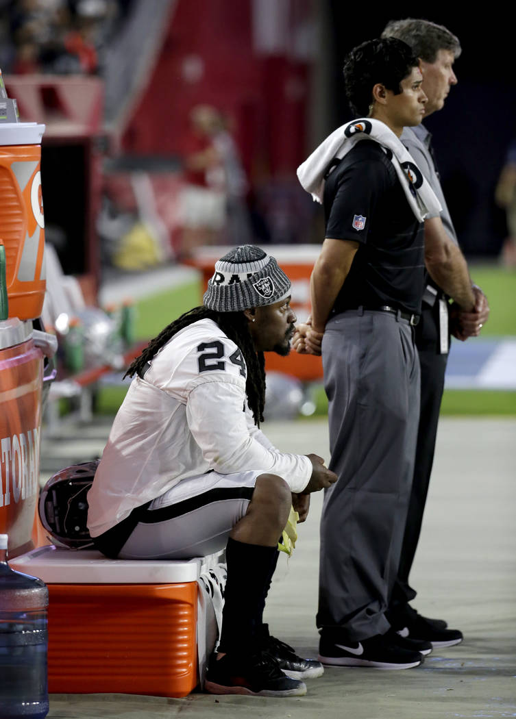 Oakland Raiders running back Marshawn Lynch (24) sits during the national anthem prior to the team's NFL preseason football game against the Arizona Cardinals, Saturday, Aug. 12, 2017, in Glendale ...