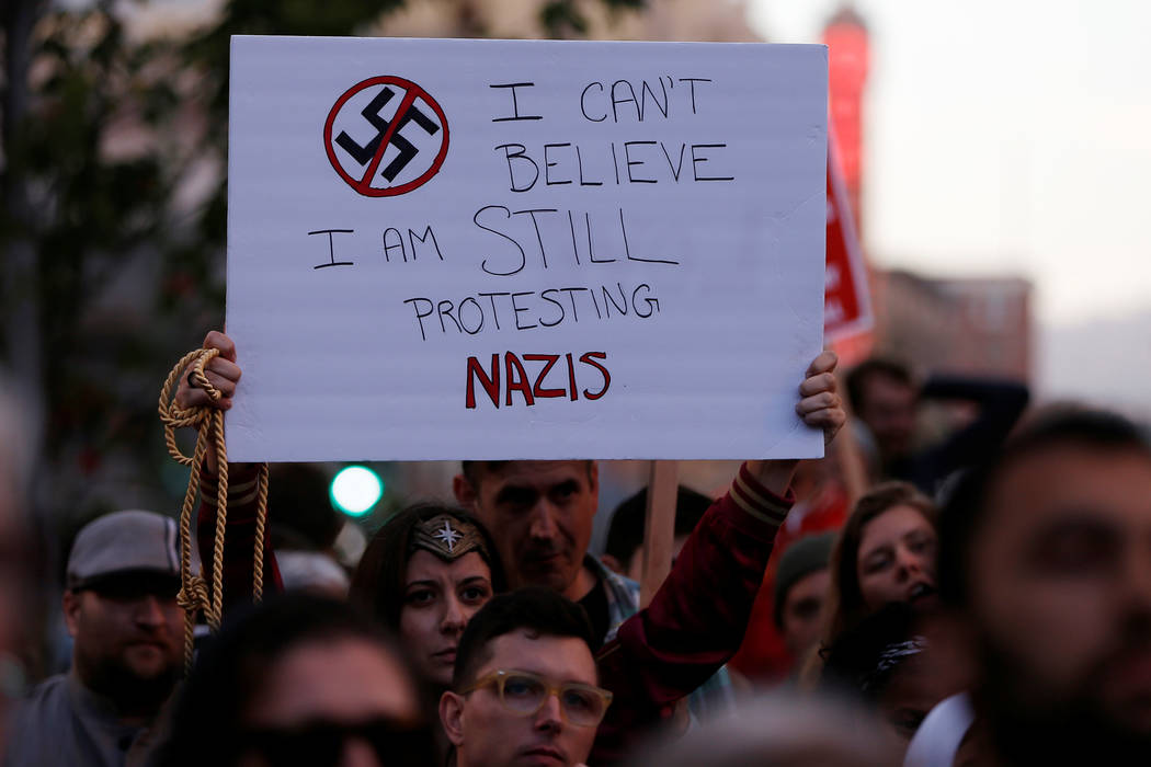 "A demonstrator holds signs during a rally in response to the Charlottesville, Virginia, car attack on counter-protesters after the ""Unite the Right"" rally organized by white nationalists, in Oakla ..."