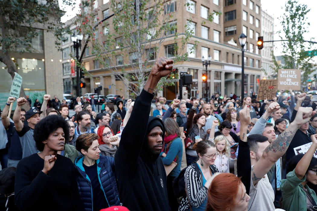 "Demonstrators gesture in response to the Charlottesville, Virginia, car attack on counter-protesters after the ""Unite the Right"" rally organized by white nationalists, in Oakland, California, Augu ..."