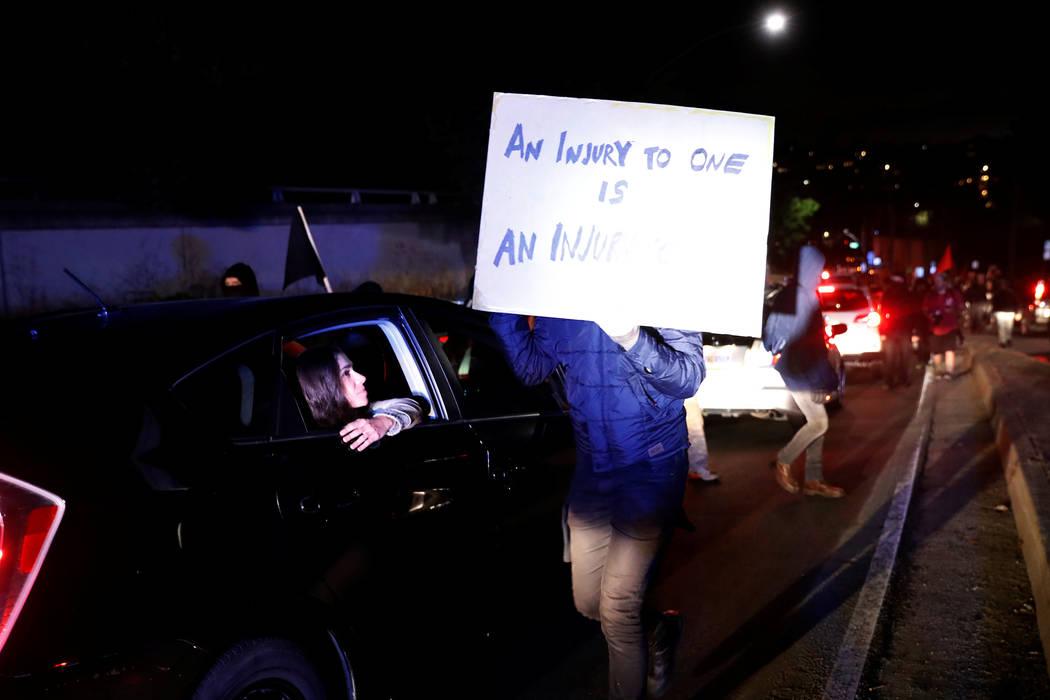 "A passenger from a stranded car looks on as demonstrators march to block Interstate 580 during a rally in response to the Charlottesville, Virginia, car attack on counter-protesters after the ""Uni ..."