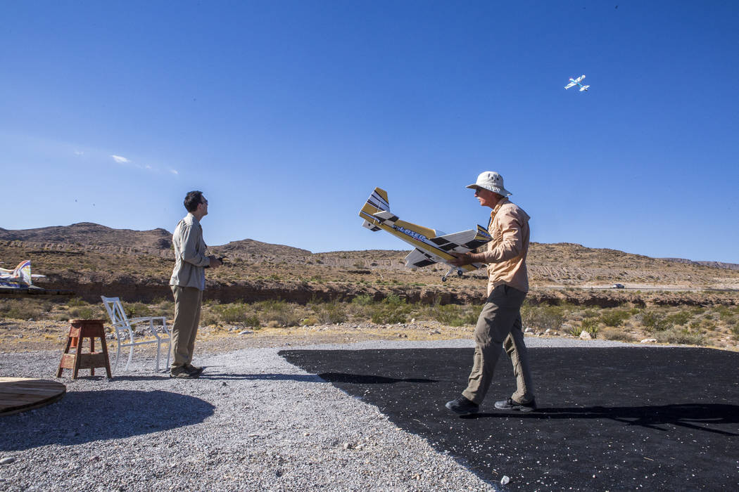 Jim Winn, right, carries his remote-controlled airplane while his son, Brody Winn, flies his airplane at the Las Vegas Soaring Club field near Red Rock Canyon on Sunday, Aug. 13, 2017.  Patrick Co ...