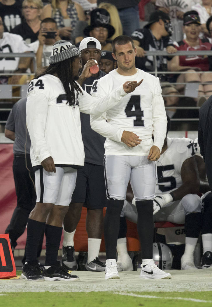 Oakland Raiders running back Marshawn Lynch (24) with quarterback Derek Carr (4) on the sideline during the first quarter of a NFL preseason game against the Arizona Cardinals in Glendale, Ariz.,  ...