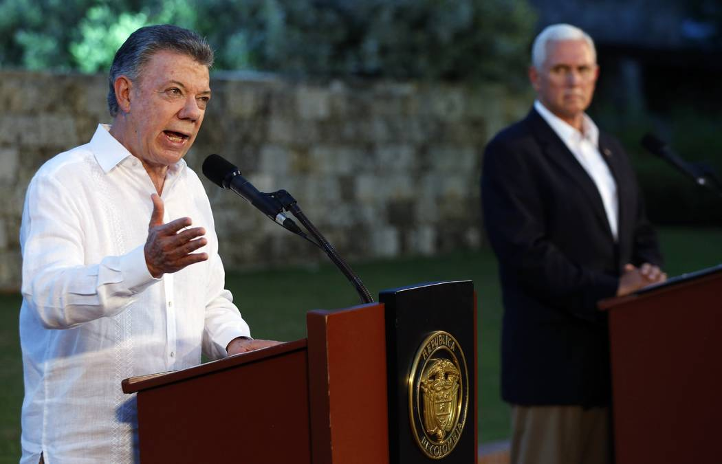 Colombia's President Juan Manuel Santos, left, talks to the media as U.S. Vice President Mike Pence listens during a joint press conference at the presidential guesthouse in Cartagena, Colombia, S ...