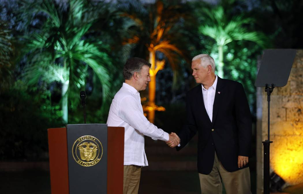 U.S. Vice President Mike Pence, right, shakes hands with Colombia's President Juan Manuel Santos during a join press conference at the presidential guesthouse in Cartagena, Colombia, Sunday, Aug.  ...
