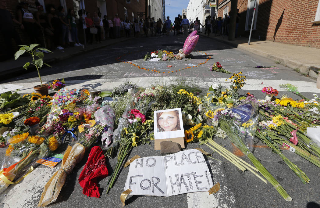 A makeshift memorial of flowers and a photo of victim, Heather Heyer, sits in Charlottesville, Va., Sunday, Aug. 13, 2017. Heyer died when a car rammed into a group of people who were protesting t ...