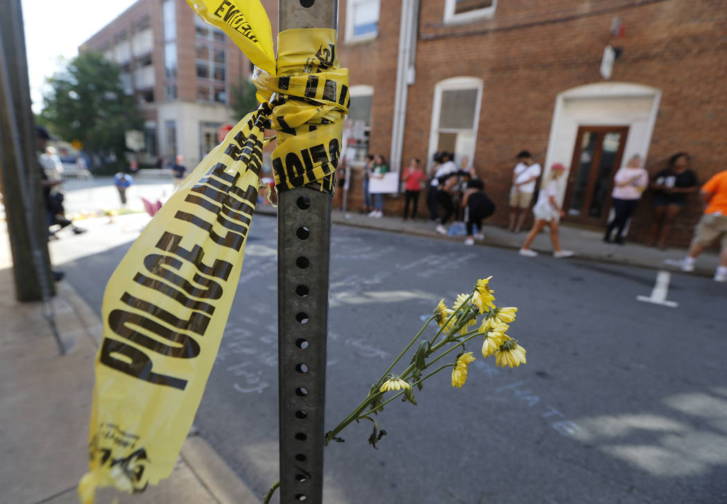 On Sunday, Aug. 13, 2017, police tape and flowers mark the site where a car plowed into a crowd of people protesting a white nationalist rally on Saturday in Charlottesville, Va. (AP Photo/Steve H ...