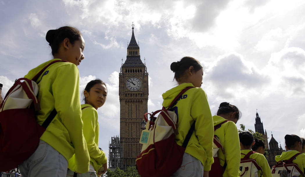 Chinese tourists walk past the Palace of Westminster and the Queen Elizabeth Tower in London, Monday, Aug. 14, 2017. Big Ben will fall silent next week in London as a major restoration project get ...