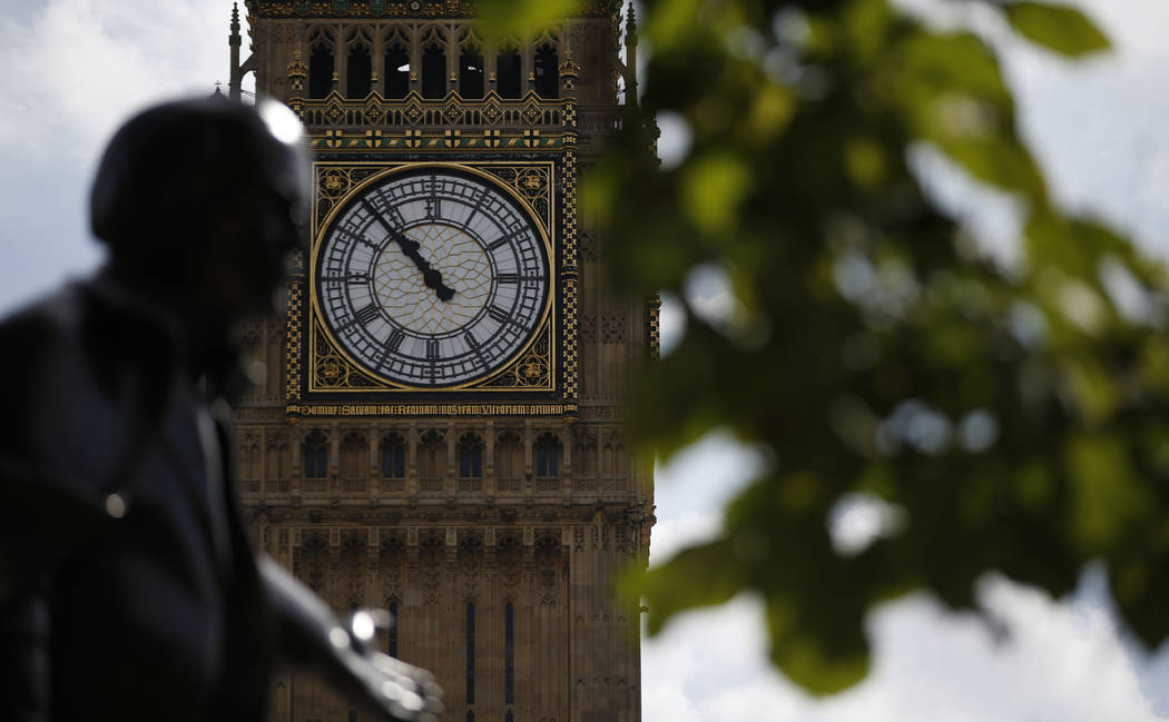 The statue of former British Prime Minister David Lloyd George is silhouetted against the Queen Elizabeth Tower which holds the bell known as 'Big Ben' in London, Monday, Aug. 14, 2017. (AP Photo/ ...