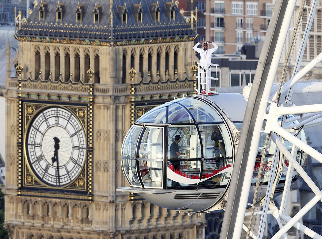 British athlete Mo Farah stands atop of a pod on the London Eye, with Big Ben's clock tower in background, as he bids a final farewell to British track competitive athletics after winning gold in  ...