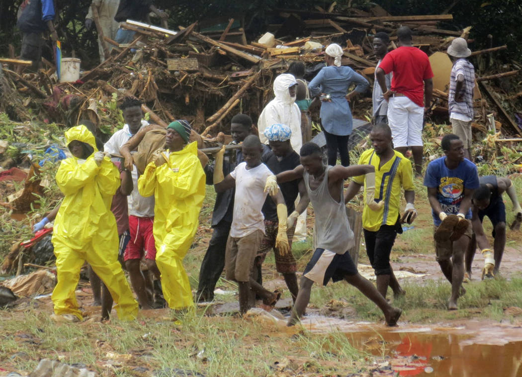 Rescue workers carry the body of a victim from the site of a mudslide in Regent, east of Freetown, Sierra Leone, Monday, Aug. 14, 2017. Mudslides and torrential flooding has killed many people in  ...